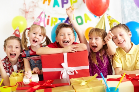 children party: Group of adorable kids looking at camera with giftboxes near by