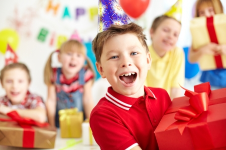 children party: Joyful boy with giftbox looking at camera with his friends on background