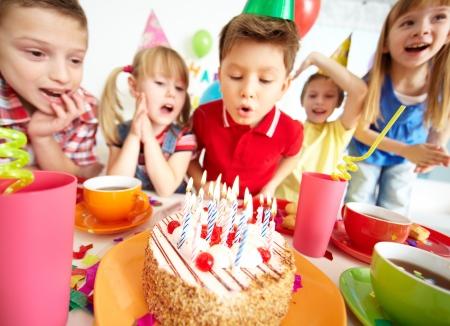 velas de cumplea�os: Grupo de ni�os adorables que mira la torta de cumplea�os con velas