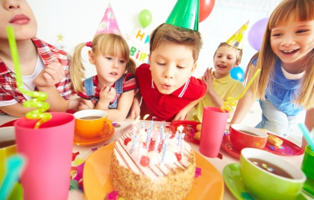 company party: Group of adorable kids gathered around birthday cake with candles Stock Photo