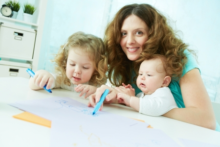 Cheerful family of three being occupied with drawing photo