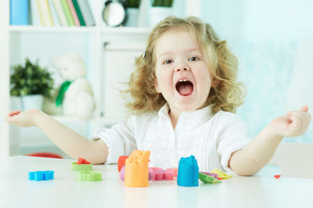 clay modeling: Happy child enjoying herself modeling with colorful clay