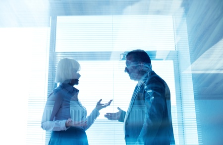 Outlines of mature businessman and his colleague communicating by the window in office photo