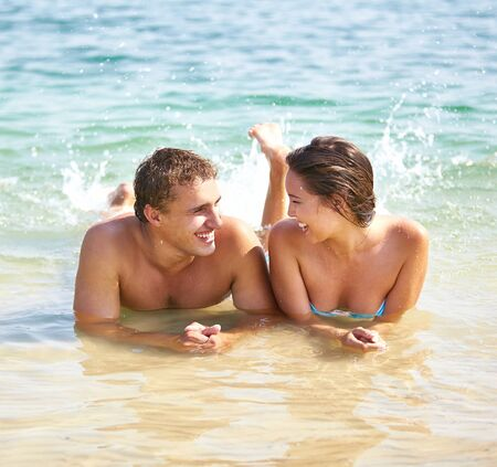 couples outdoors: Guy and girl having fun lying in water and splashing