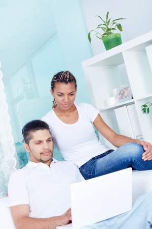 Image of young guy and his girlfriend using laptop at home Stock Photo - 19146660
