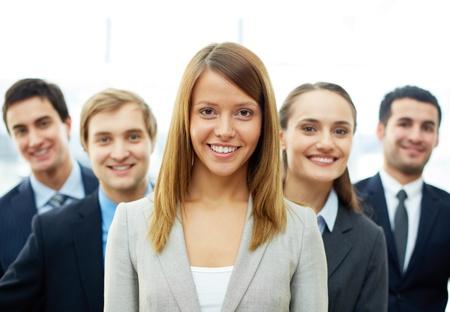 lideres: Feliz empresaria mirando la cámara con socios inteligentes detrás