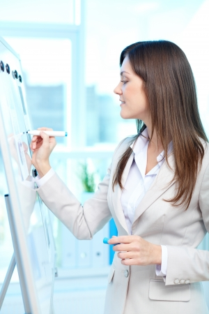 business attire teacher: Portrait of a lovely young businesswoman writing on board with highlighter
