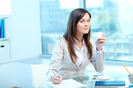 proficiency: Portrait of young female drinking tea while writing proficiency test Stock Photo