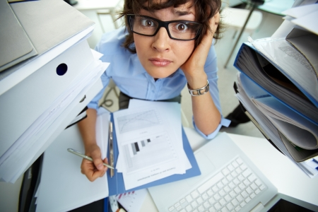 is embarrassed: Perplexed accountant doing financial reports surrounded by huge piles of documents