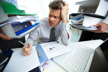 workaholic: Perplexed accountant looking at huge piles of documents held by his business partners while doing financial reports Stock Photo