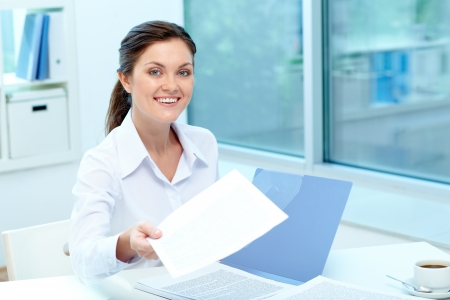 Portrait of happy employer giving test results to applicant photo
