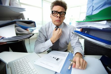 Shocked accountant looking at camera surrounded by huge piles of documents held by his partners photo
