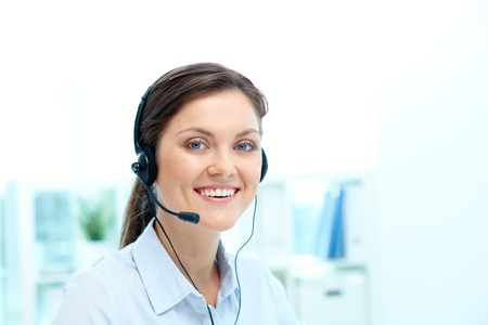 Portrait of young operator with headset looking at camera with friendly smile Stock Photo - 19170121
