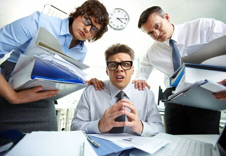 Pleading accountant looking at camera being surrounded by his partners with huge piles of documents photo