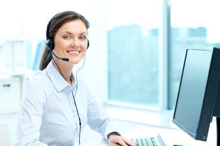 Portrait of young operator with headset looking at camera with friendly smile Stock Photo - 19177559