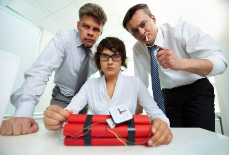 human time bomb: Group of businesspeople with dynamite looking at camera in office  Stock Photo