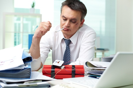 detonator: Smoking businessman looking at hand-crafted bomb in office Stock Photo