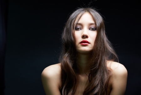 Young woman looking at camera over black background Stock Photo