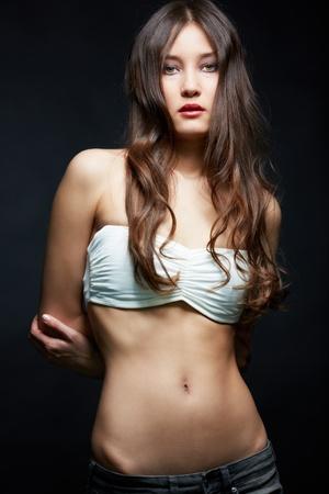 f�minit�: Slim fille regardant la cam�ra sur fond noir