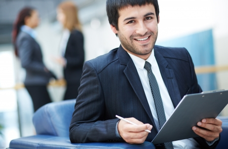 Portrait of friendly male leader looking at camera in working environment Stock Photo - 19170140