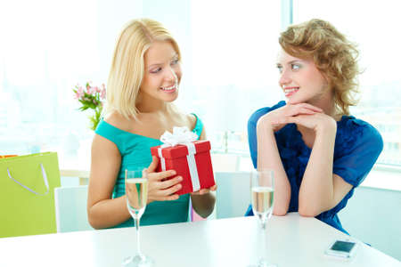 Young woman showing birthday surprise to her friend