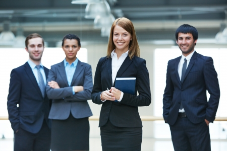 young executives: Group of smart businesspeople with happy female leader in front