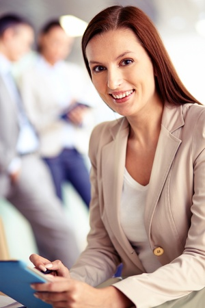 Portrait of friendly specialist looking at camera on the background of working colleagues photo