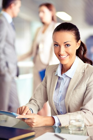 Portrait of confident employee working with touchpad on background of working colleagues photo