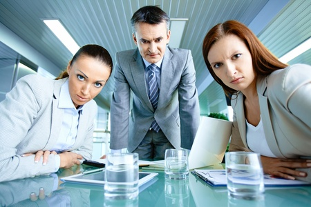tense: Serious boss with his two employees looking at camera with displeasure