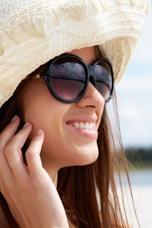 Portrait of pretty young lady in hat and sunglasses photo