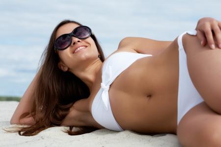 Image of female in white bikini sunbathing on sandy beach photo