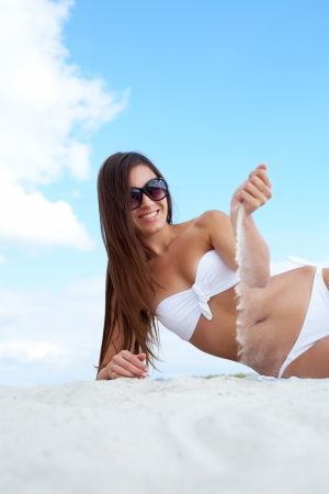 Image of female in white bikini playing with sand while sunbathing on sandy beach Stock Photo - 19160673