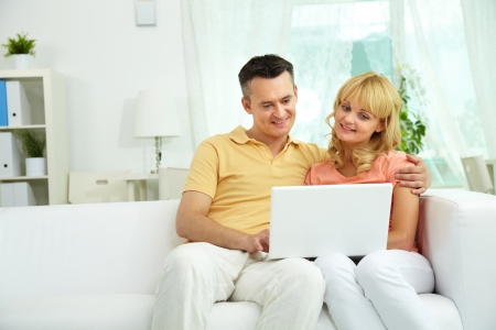 Image of happy couple sitting on the sofa and looking at laptop   Stock Photo - 19178386