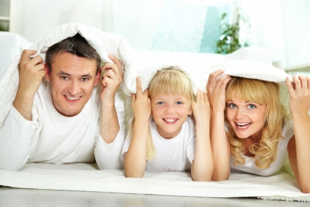 Portrait of happy parents and their daughter with blanket above their heads Stock Photo - 19177610