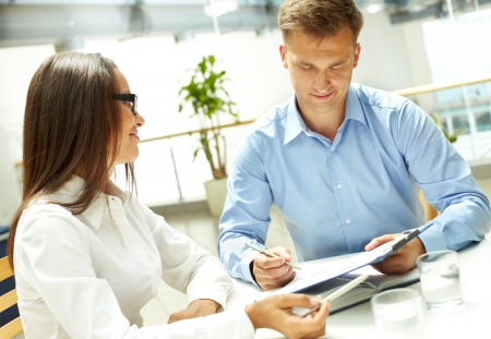 Young businesswoman looking at her business partner explaining document photo