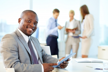 people interacting: Portrait of happy leader with touchpad looking at camera in working environment Stock Photo
