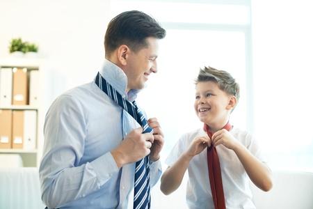 Foto van gelukkige jongen en zijn vader binden stropdassen