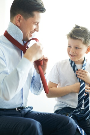 Photo of happy boy looking at his father while learning how to tie necktie