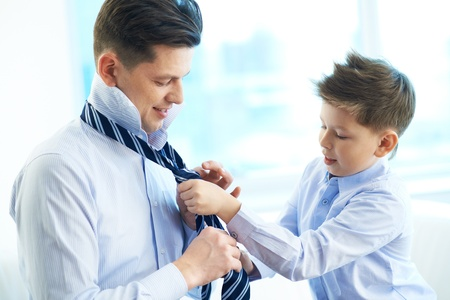 Photo of little boy helping his father tie necktie photo