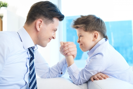 family fight: Photo of little boy and his dad armwrestling