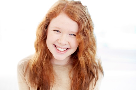 ginger hair: Teenage girl with wavy ginger hair looking at camera with smile