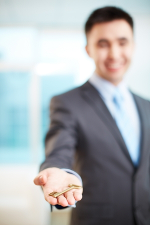 Hand of businessman holding key photo
