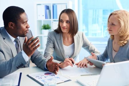 conversation: Pretty business interns listening to their team leader Stock Photo