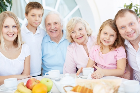 male senior adult: Portrait of senior and young couples with their children having dinner at home