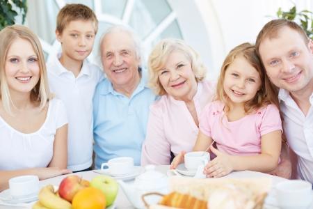 abuelos: Retrato de senior y jóvenes parejas con sus hijos que tienen la cena en casa