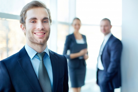 business leader: Male leader looking at camera with his partners on background Stock Photo
