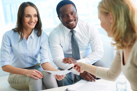 multi ethnic: Young businesswoman asking her partners sign paper at meeting
