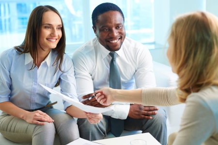 Young businesswoman showing her partners contract at meeting photo