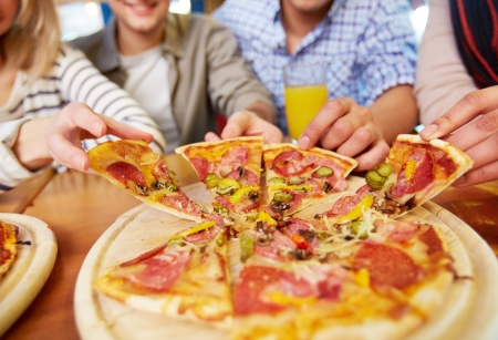 delicious: Image of teenage friends hands taking slices of pizza Stock Photo