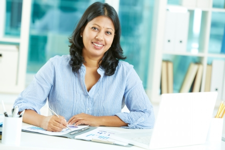 indian: Portrait of happy mature businesswoman looking at camera while working in office Stock Photo